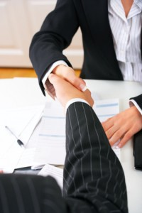 Closing a deal with a handshake. Signed contract on the table.